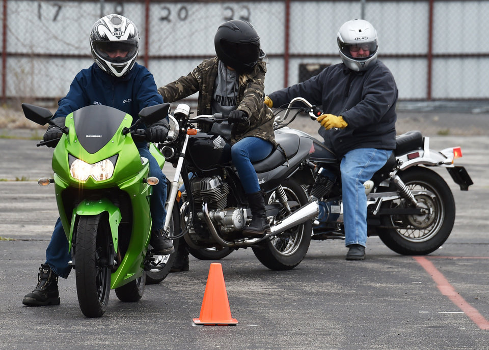 Photo -  Issac Moss, Michelle Carroll and Kevin Ward wait at the start of the course during the Precision Driving School motorcycle training class in Norman. [Photo by Tyler Drabek, For The Oklahoman]