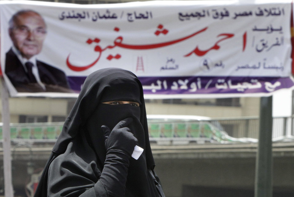 Photo -   An Egyptian woman wearing an Islamic Niqab, or face veil, walks under banners supporting Presidential candidate Ahmed Shafiq in Cairo, Egypt, Tuesday, May 22, 2012. The May 23-24 presidential election is the first since last year's ouster of longtime authoritarian ruler Hosni Mubarak, marking the first time Egyptians will choose their leader in a race overseen by international monitors. The Arabic writing reads,