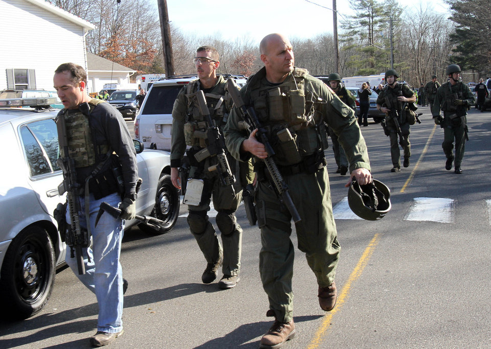 Photo - Heavily armed Connecticut State troopers are on the scene at the Sandy Hook School in Newtown, Conn. where authorities say a gunman opened fire, leaving 27 people dead, including 20 children, Friday, Dec. 14, 2012.  (AP Photo/The Journal News, Frank Becerra Jr.) MANDATORY CREDIT, NYC OUT, NO SALES, TV OUT, NEWSDAY OUT; MAGS OUT ORG XMIT: NYWHI118