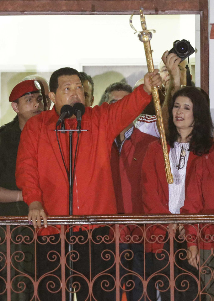 Venezuela's President Hugo Chavez, left, hods up ta replica of Simon Bolivar's sword as he greets supporters from the Miraflores presidential palace balcony in Caracas, Venezuela, Sunday, Oct. 7, 2012. Chavez won re-election and a new endorsement of his socialist project Sunday, surviving his closest race yet after a bitter campaign against opposition candidate Henrique Capriles.(AP Photo/Fernando Llano)