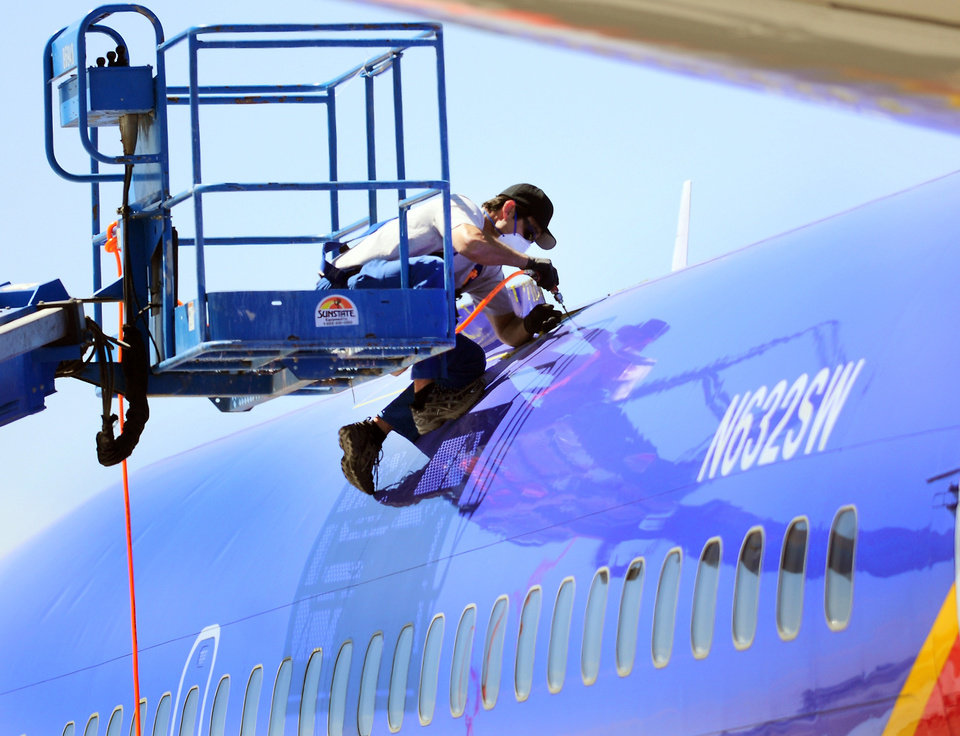 Photo - File- This April 3, 2011, file photo shows a member of the National Transportation and Safety Board investigating the emergency landing of Southwest Airlines flight 812 cutting away a portion of the planes fuselage in Yuma, Ariz.  (AP Photo/The Yuma Daily Sun, Craig Fry, File)