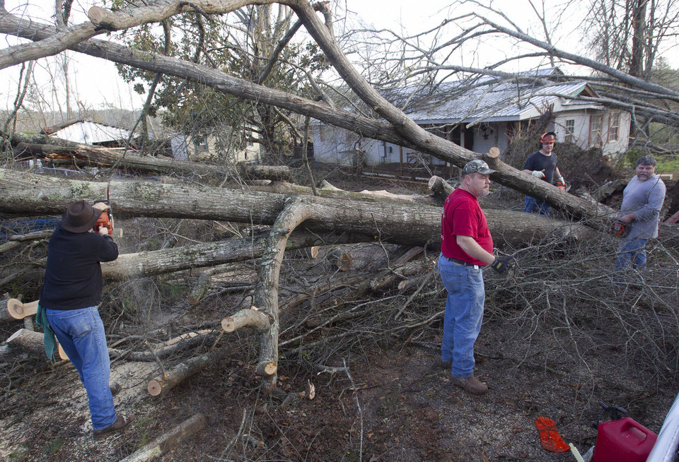 Residents cut fallen trees off of houses in Oak Grove, Ala., Monday, Jan. 23, 2012. after a  possible tornado passed through the area. Homes were flattened, windows were blown out of cars and roofs were peeled back in the middle of the night in the community of Oak Grove near Birmingham.  (AP Photo/Dave Martin) ORG XMIT: ALDM105