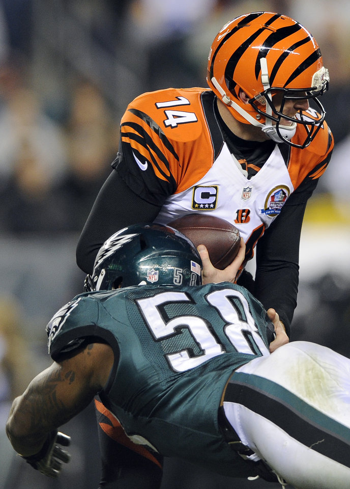 Cincinnati Bengals' Andy Dalton, top, is sacked by Philadelphia Eagles' Trent Cole in the first half of an NFL football game, Thursday, Dec. 13, 2012, in Philadelphia. (AP Photo/Michael Perez)