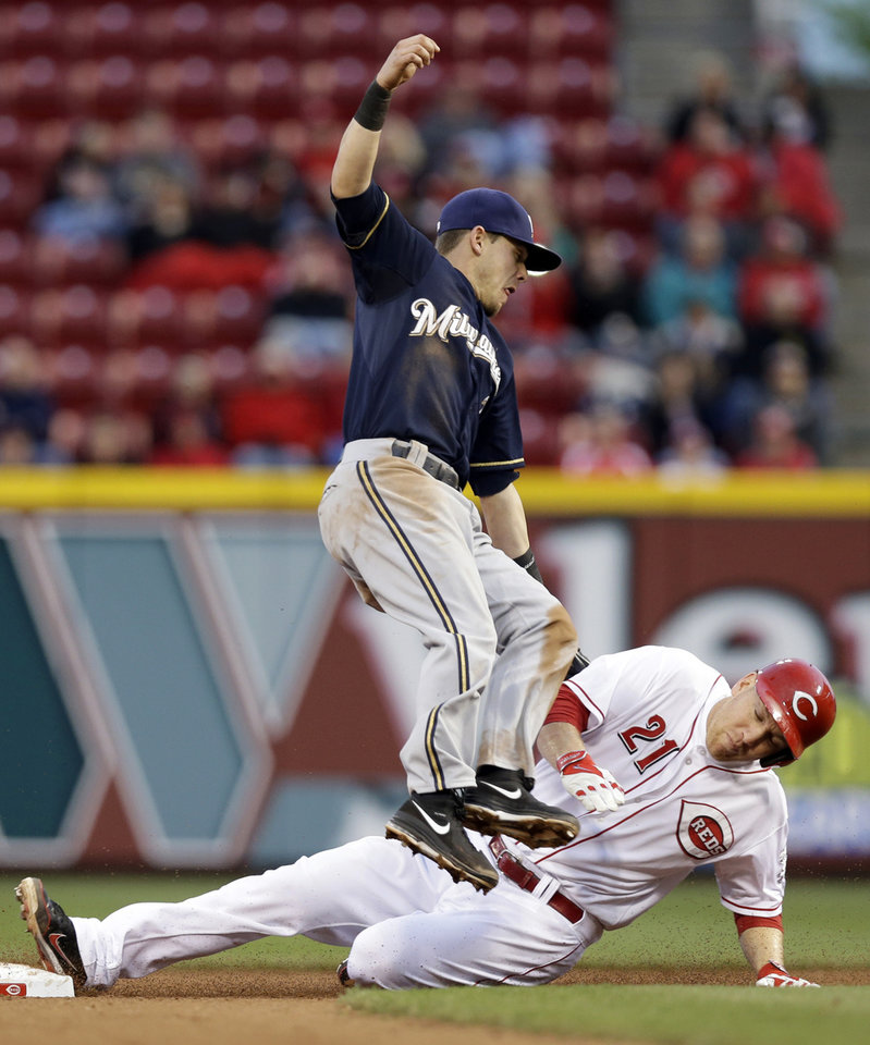 Photo - Milwaukee Brewers second baseman Scooter Gennett tries to tag Cincinnati Reds' Todd Frazier (21) stealing second base in the fourth inning of a baseball game, Thursday, May 1, 2014, in Cincinnati. (AP Photo/Al Behrman)