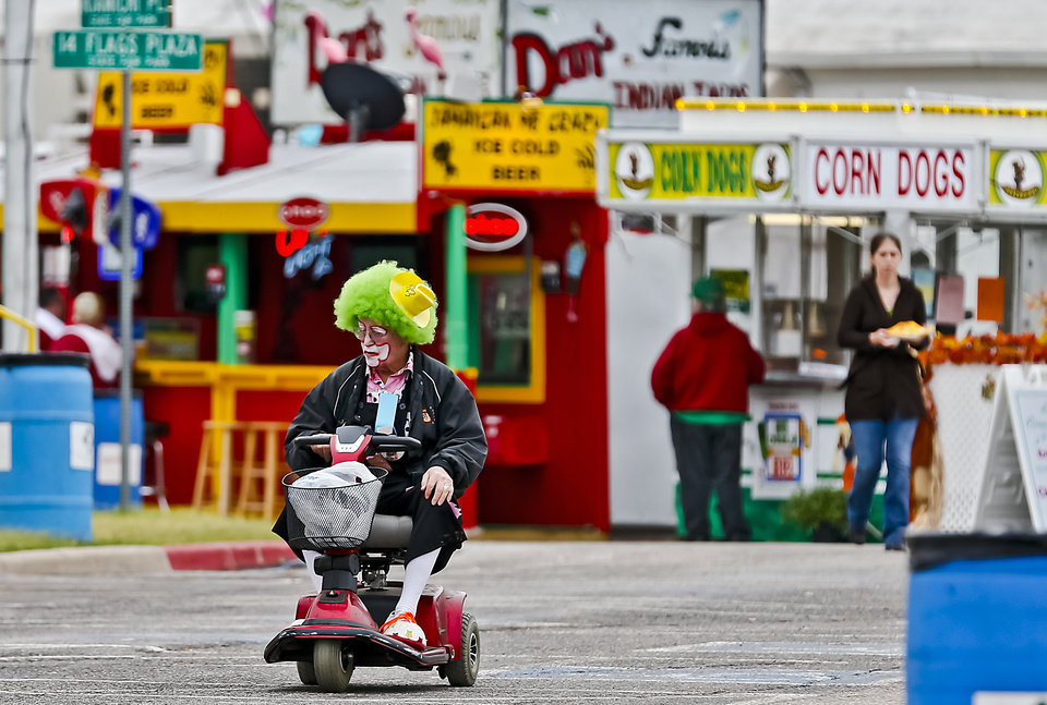 Photo - A Shriner clown uses a scooter to make his way through the fair at the Oklahoma State Fair at State Fair Park on Friday, Sept. 14, 2012, in Oklahoma City, Oklahoma.  Photo by Chris Landsberger, The Oklahoman