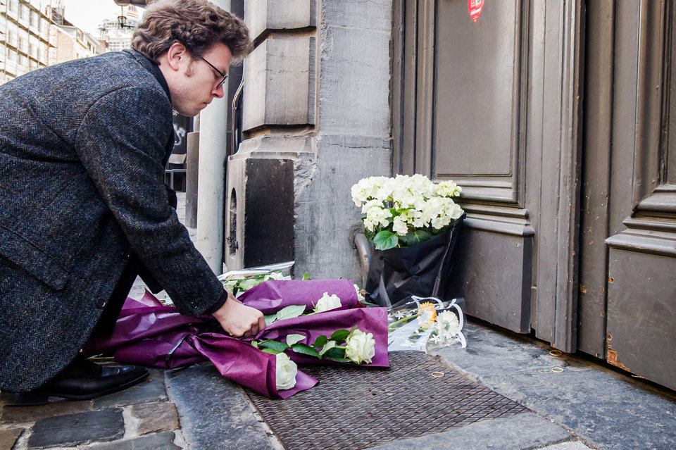 Photo - A man lays flowers at the Jewish Museum in Brussels, Sunday May 25, 2014.  Police stepped up security at Jewish institutions, schools and synagogues after three people were killed and one seriously injured in a spree of gunfire at the Jewish Museum in Brussels on Saturday. (AP Photo/Geert Vanden Wijngaert)