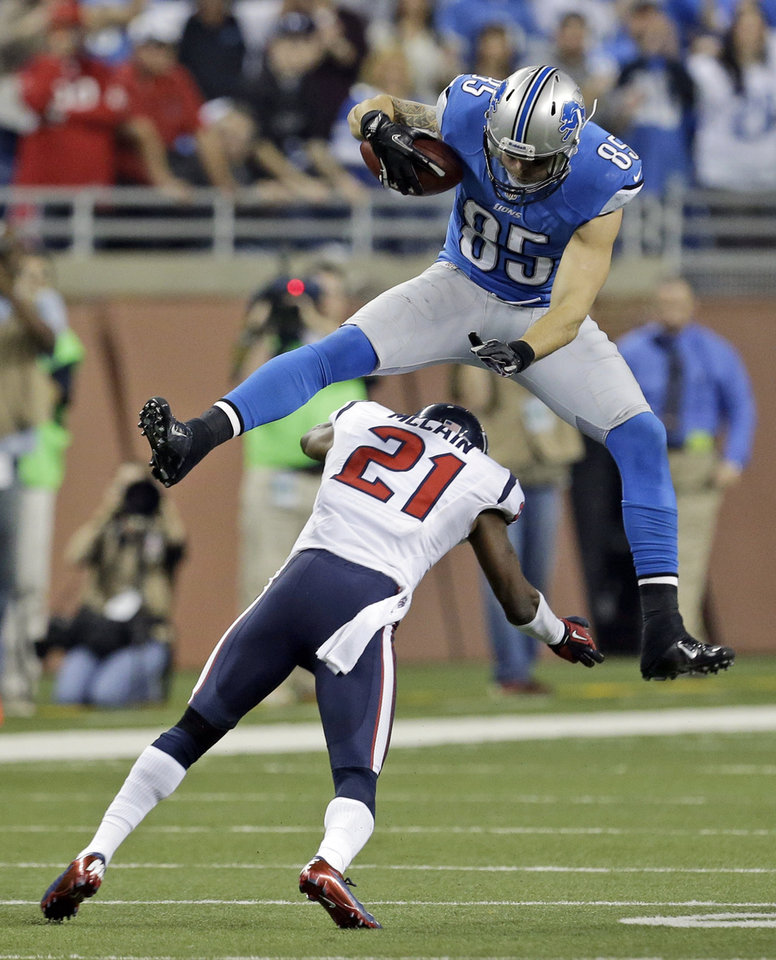 Photo -   Detroit Lions tight end Tony Scheffler (85) jumps over Houston Texans defensive back Brice McCain (21) during overtime of an NFL football game at Ford Field in Detroit, Thursday, Nov. 22, 2012. (AP Photo/Paul Sancya)