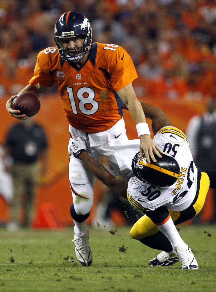 Denver Broncos quarterback Peyton Manning (18) is wrapped up by Pittsburgh Steelers linebacker Larry Foote (50) during the second quarter of an NFL football game, Sunday, Sept. 9, 2012, in Denver. (AP Photo/David Zalubowski)