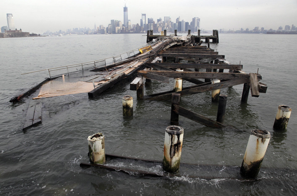 Photo - Manhattan island is visible behind the auxiliary pier on Liberty Island, damaged by Superstorm Sandy, in New York,  Friday, Nov. 30, 2012. Tourists in New York will miss out for a while on one of the hallmarks of a visit to New York, seeing the Statue of Liberty up close. Though the statue itself survived Superstorm Sandy intact, damage to buildings and Liberty Island's power and heating systems means the island will remain closed for now, and authorities don't have an estimate on when it will reopen. (AP Photo/Richard Drew)