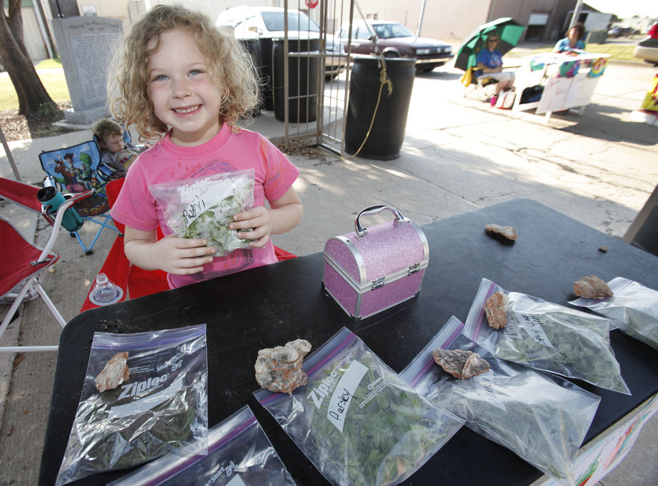 Photo - Allie Anhalt, 6, shows herbs she grew and sells at the Junior Market at Edmond's Festival Market Place. She donates the proceeds to Oklahoma Center for Autism.