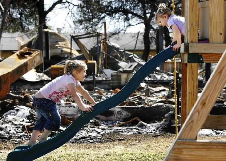 Sisters Cheyann, 5, and Sara Ford, 3, play on a wooden swing set that escaped the flames. The girls were visiting their grandmother who lives next door to this burned house. The grandmother's house, 1004 Pacific, received minor damage. FEMA toured several neighborhoods on Tuesday, April 14, 2009. Photo by JIM BECKEL
