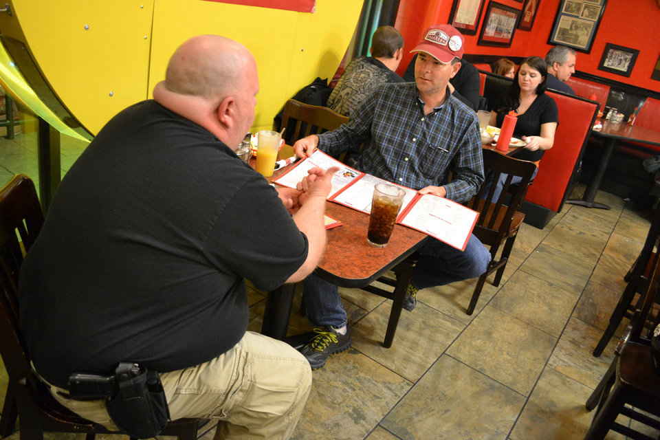 Photo - Dustin Merritt, left, of Noble, and Joe Wood, of Norman, carry handguns in holsters on their belts while they catch a midnight snack at Beverly's Pancake House in Oklahoma City on Thursday.  Zeke Campfield - Oklahoman