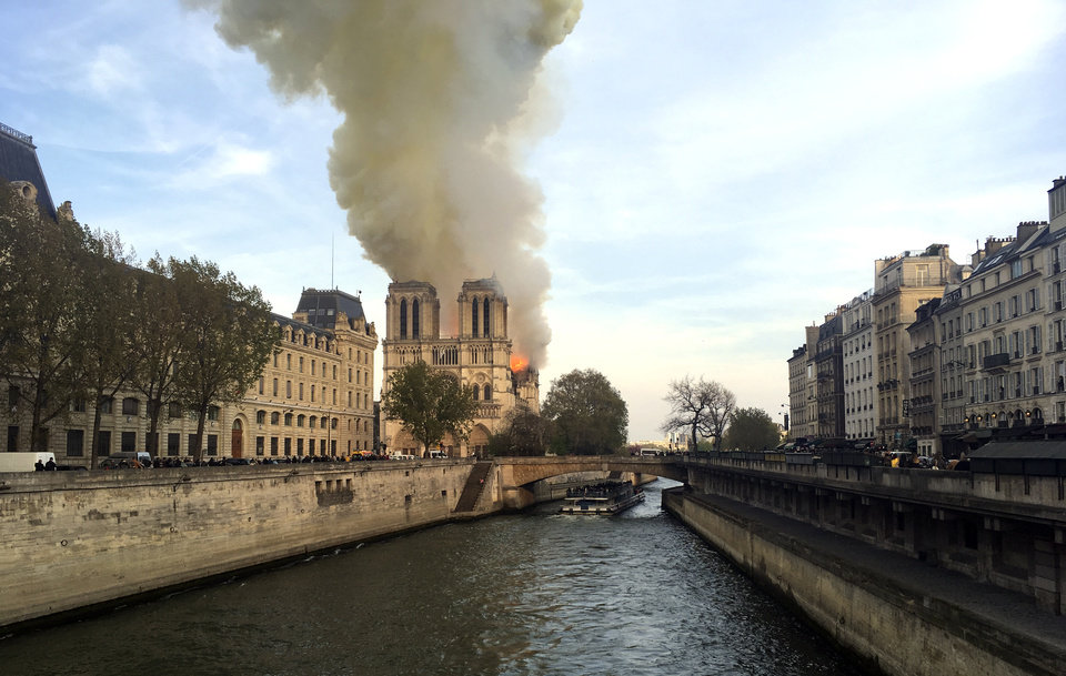 Photo - Notre Dame cathedral is burning in Paris, Monday, April 15, 2019. Massive plumes of yellow brown smoke is filling the air above Notre Dame Cathedral and ash is falling on tourists and others around the island that marks the center of Paris. (AP Photo/Lori Hinant)