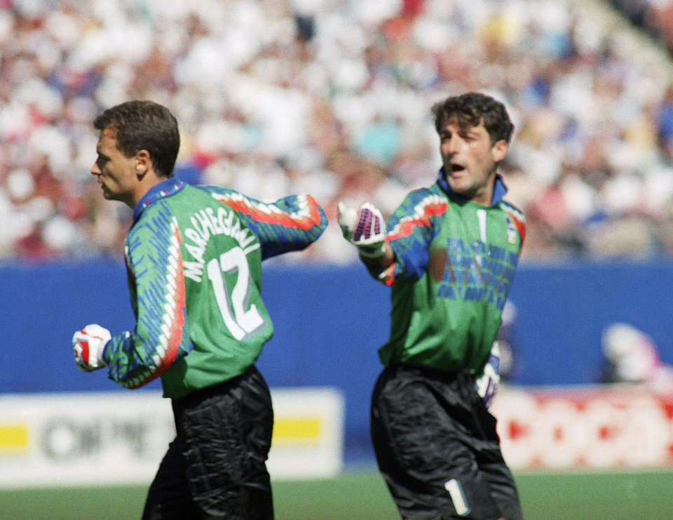 FILE - In this Thursday, June 23, 1994 file photo, Italy\'s goalkeeper Gianluca Pagliuca, right, passes substitute keeper Luca Marchegiani, left, as Pagliuca leaves the field of play after receiving a red card during the World Cup Group E opening round soccer match against Norway, at Giants Stadium in East Rutherford, N.J. On this day: Italy's Pagliuca becomes the first goalkeeper to be sent off in a World Cup finals match. Italy still prevailed 1-0. (AP Photo/Gianni Foggia, File)