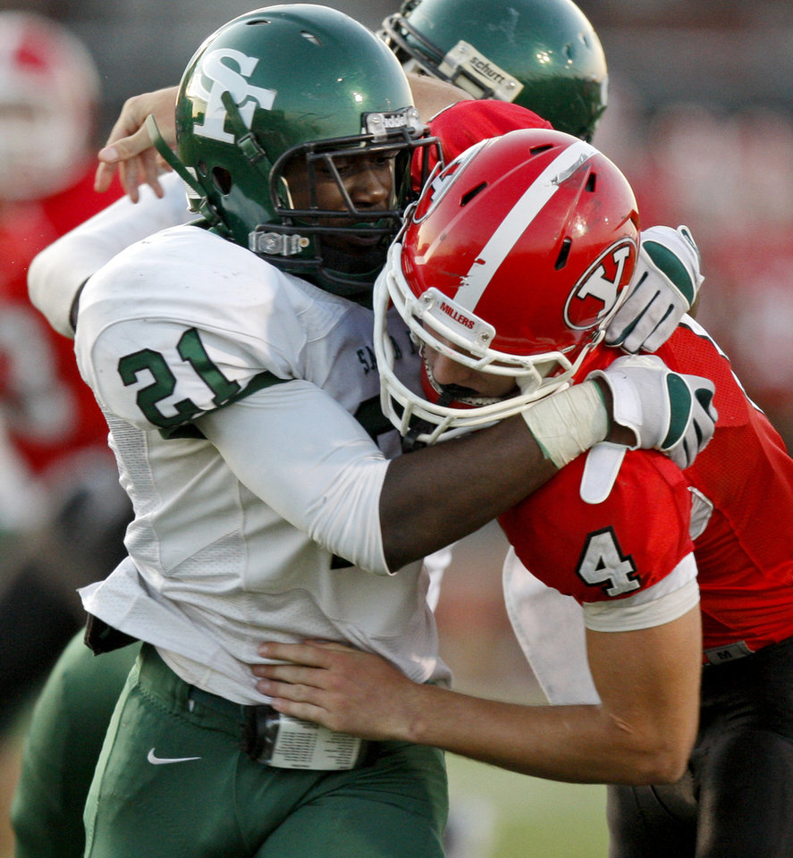 Edmond Santa Fe's Ryan Frazier hits Yukon's Corben Jones as he throws a interception during a high school football game in Yukon, Okla., Friday, Sept. 9, 2011. Photo by Bryan Terry, The Oklahoman