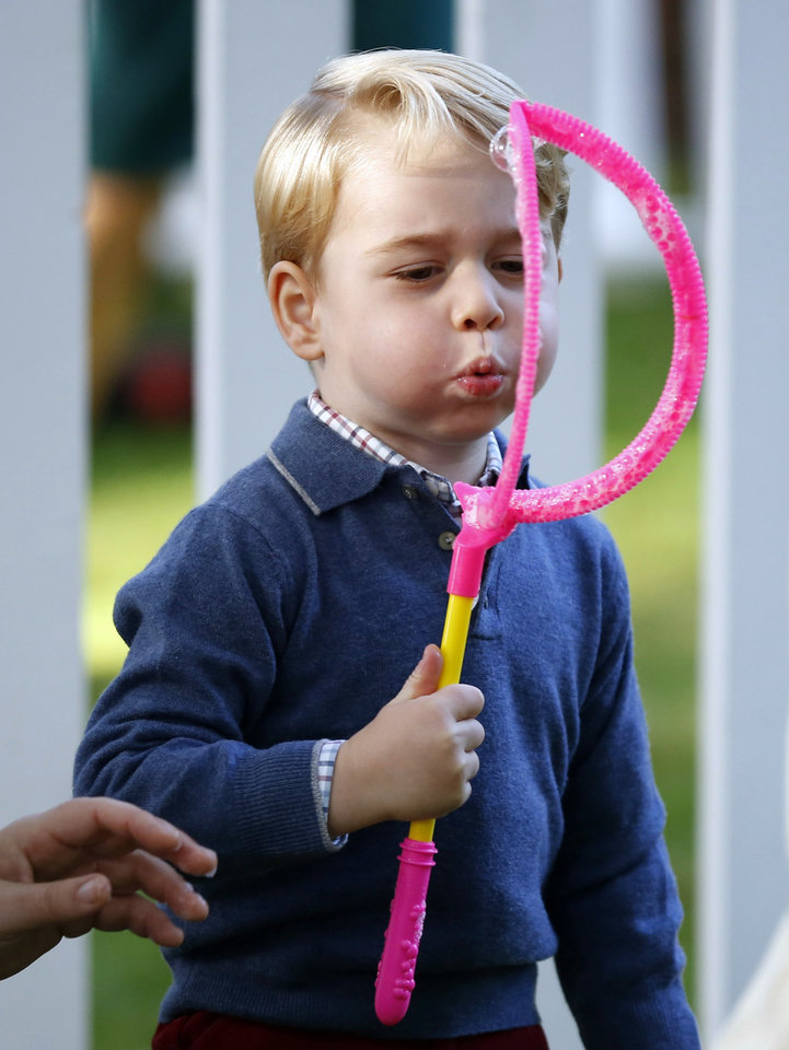 Photo - Britain's Prince George blows bubbles during a children's party at Government House in Victoria, British Columbia, Thursday, Sept. 29, 2016. (Chris Wattie/The Canadian Press via AP, Pool)