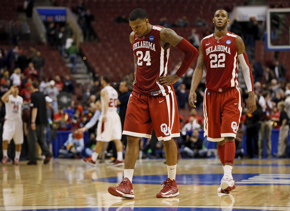 Oklahoma's Romero Osby (24) and Amath M'Baye (22) leave the court after a game between the University of Oklahoma and San Diego State in the second round of the NCAA men's college basketball tournament at the Wells Fargo Center in Philadelphia, Friday, March 22, 2013. San Diego State beat OU, 70-55. Photo by Nate Billings, The Oklahoman