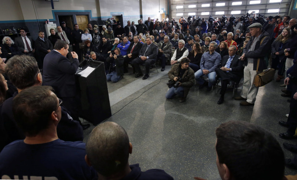 Photo - New Jersey Gov. Chris Christie, left at podium, addresses a gathering as he announces his