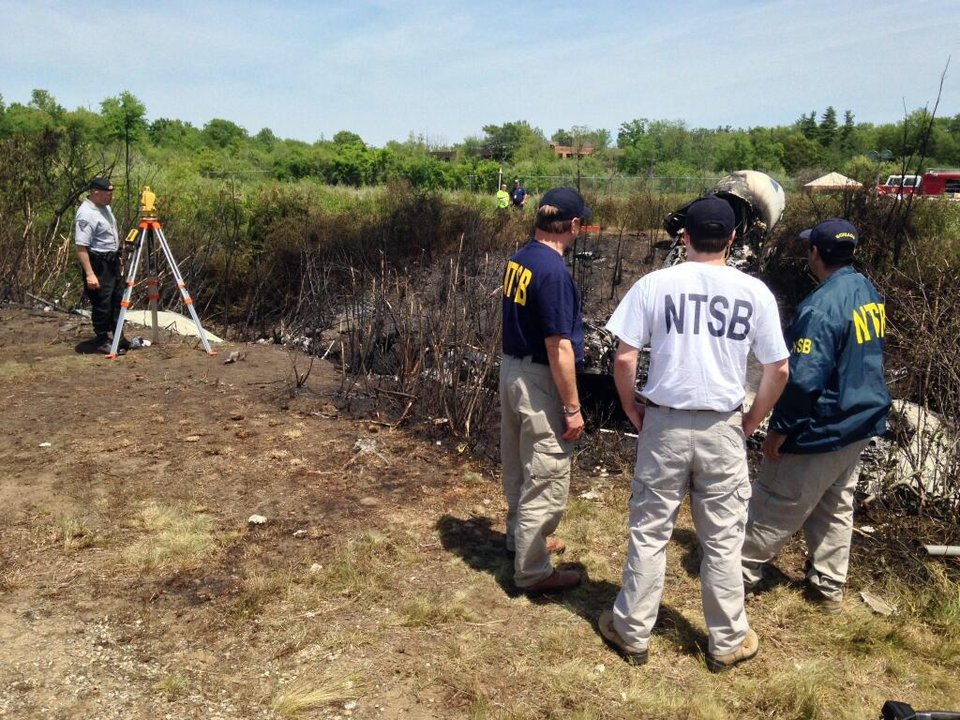 In this Sunday, June 1, 2014 photo provided by the National Transportation Safety Board, shows NTSB investigators at the scene of a plane that plunged down an embankment and erupted in flames during a takeoff attempt Saturday night at Hanscom Field in Bedford, Mass. The co-owner of the Philadelphia Inquirer newspaper, Lewis Katz, was killed along with six other people in the crash just days after reaching a deal that many hoped would end months of infighting at the newspaper and help restore it to its former glory. (AP Photo/National Transportation Safety Board)