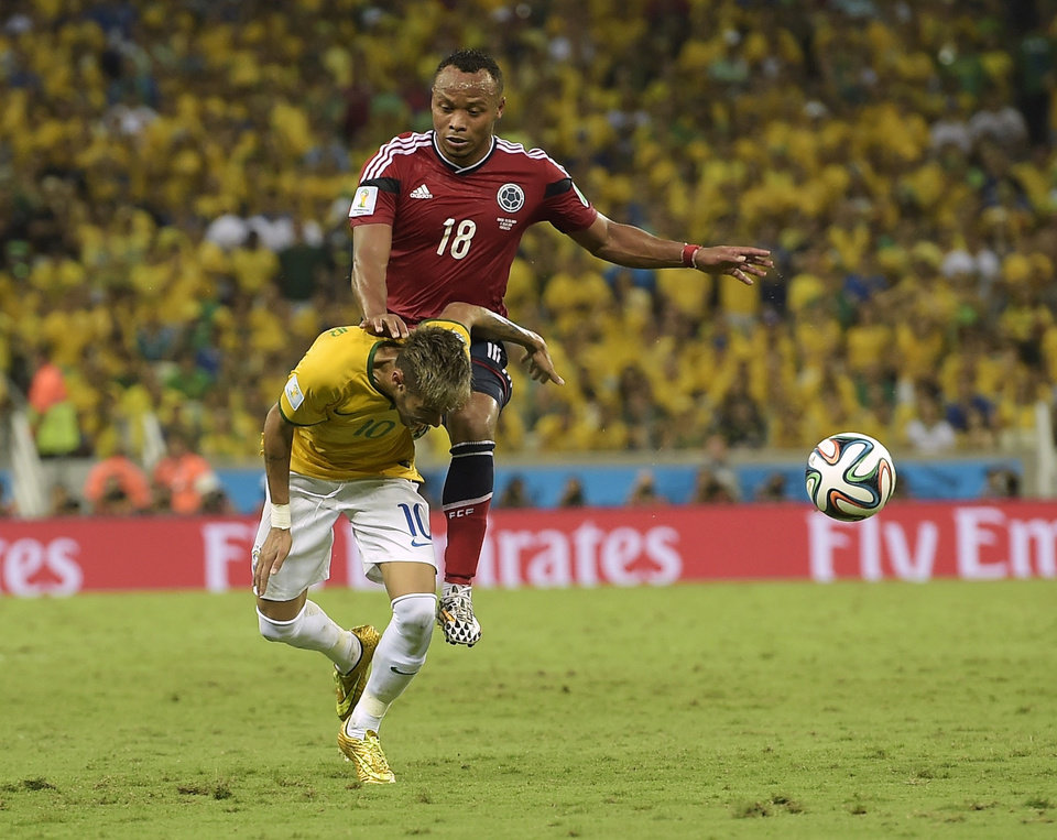 Photo - Brazil's Neymar is fouled by Colombia's Juan Zuniga during the World Cup quarterfinal soccer match between Brazil and Colombia at the Arena Castelao in Fortaleza, Brazil, Friday, July 4, 2014. (AP Photo/Manu Fernandez)