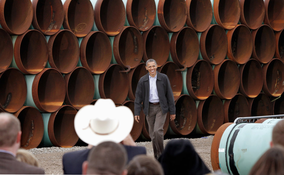 President Obama smiles when he is greeted with applause as he walks to the podium. With large oil pipe stacked 20 feet high as a backdrop, President Barack Obama delivered a speech promoting his administration\'s energy policies to a group of about 200 invited guests at a pipe storage yard just north of Ripley Thursday morning, March 22, 2012. Photo by Jim Beckel, The Oklahoman