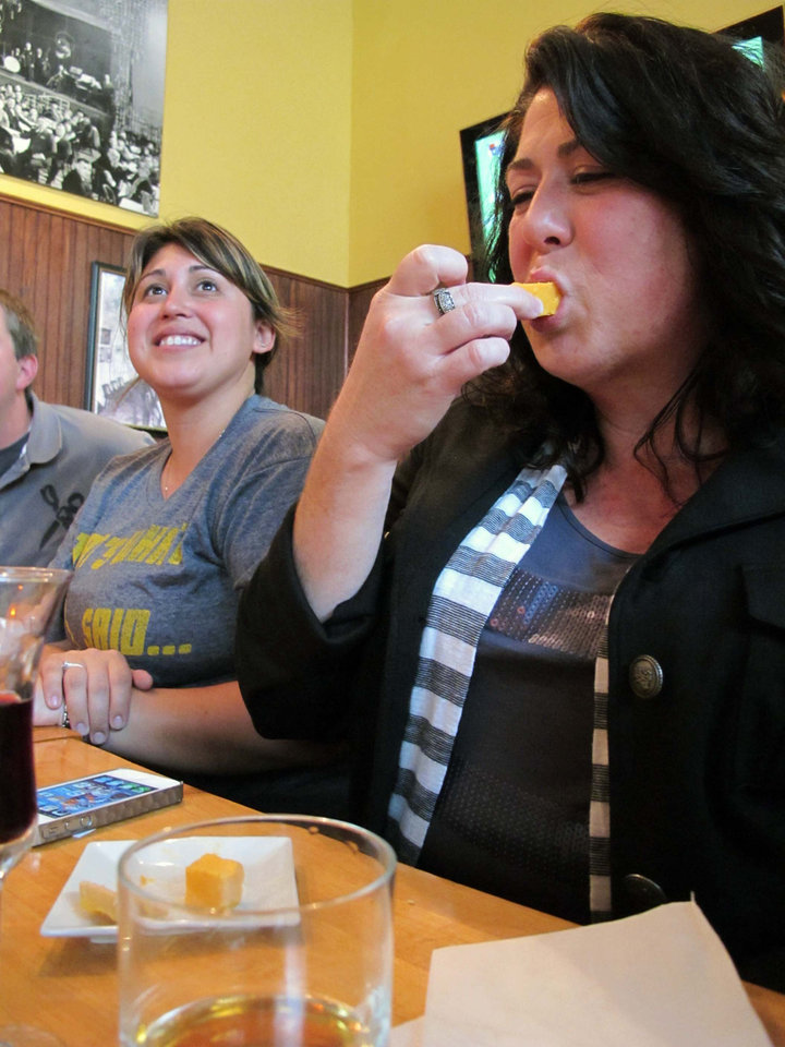 Photo -   eana Dearry, 42, of Milwaukee, tries a piece of 40-year-old cheddar on Saturday, Oct. 6, 2012 during a cheese tasting at Wisconsin Cheese Mart in Milwaukee. She described it as smooth with a clean finish. (AP Photo/Carrie Antlfinger)