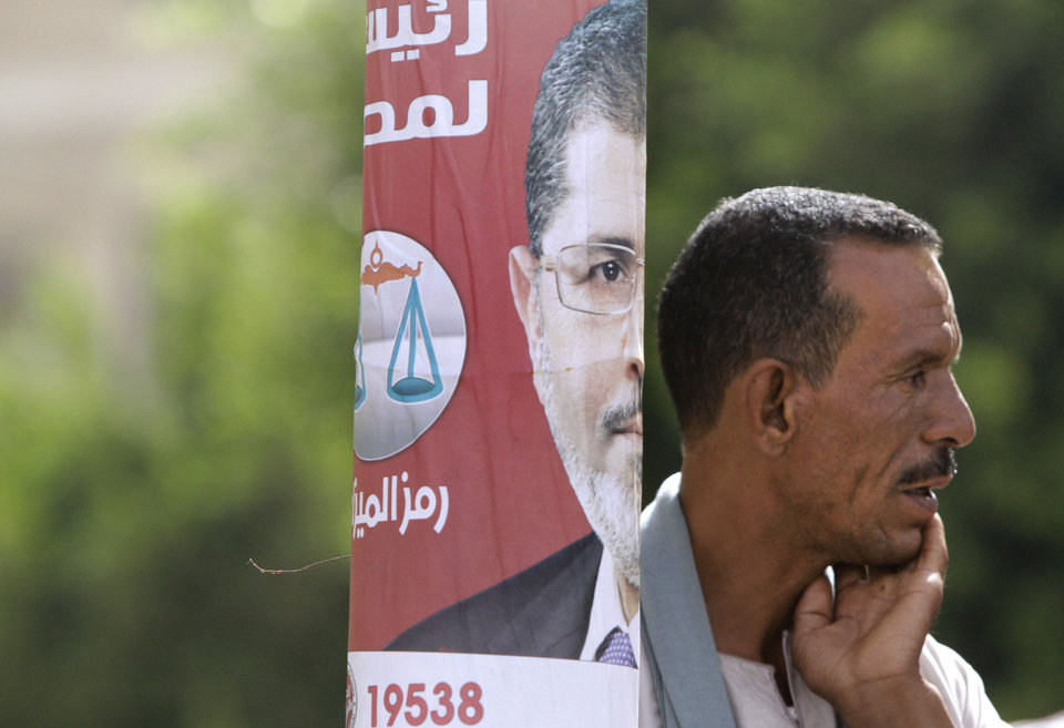 Photo -   An Egyptian stands near a poster showing Muslim brotherhood candidate Mohammed Morsi outside a polling station in Cairo, Egypt, Wednesday, May 23, 2012. Nearly a year and a half after the ouster of autocratic leader Hosni Mubarak, millions of Egyptians lined up for hours outside polling stations Wednesday to freely choose a president for the first time in an election that pits old regime figures promising stability against ascending Islamists seeking to consolidate power.(AP Photo/Amr Nabil)