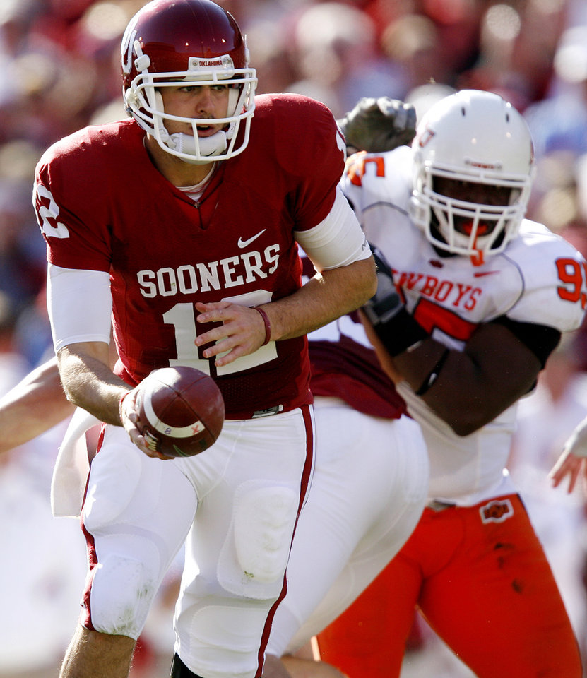 Photo - Oklahoma's Landry Jones (12) looks to hand the ball off during the first half of the Bedlam college football game between the University of Oklahoma Sooners (OU) and the Oklahoma State University Cowboys (OSU) at the Gaylord Family-Oklahoma Memorial Stadium on Saturday, Nov. 28, 2009, in Norman, Okla.Photo by Chris Landsberger, The Oklahoman
