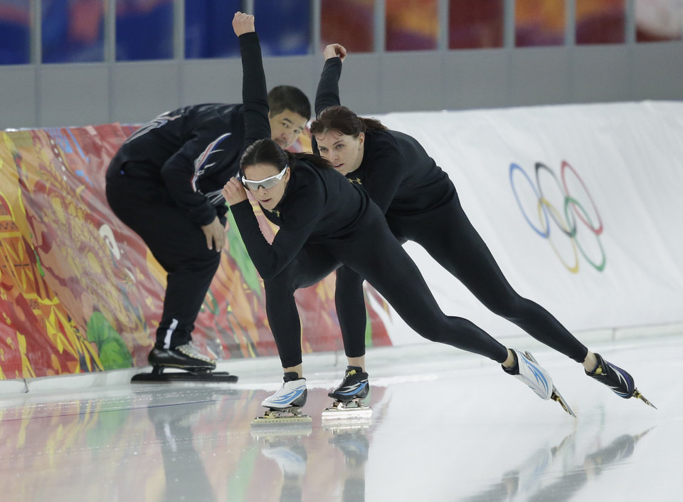 Photo - Coach Ryan Shimabukuro watches Brittany Bowe of the U.S., front, and Heather Richardson, rear, practice at the Adler Arena Skating Center at the 2014 Winter Olympics, Saturday, Feb. 15, 2014, in Sochi, Russia. (AP Photo/Patrick Semansky)