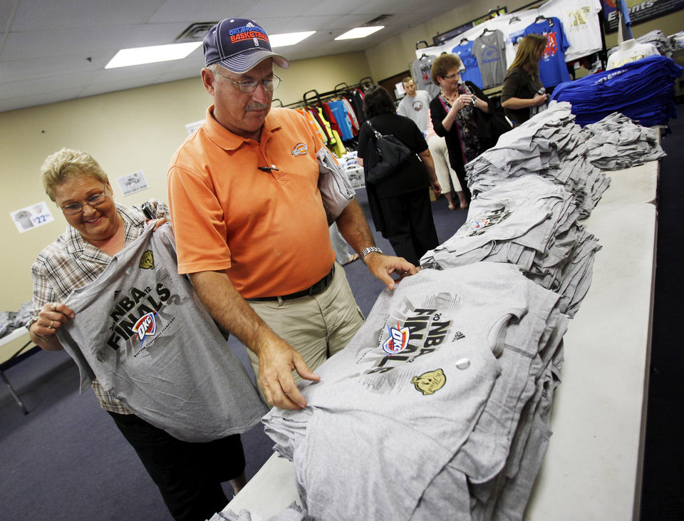 Photo - Brenda Taylor, left, and Larry Calloway look at Oklahoma City Thunder NBA Finals shirts at the USA Screen Printing and Embroidery's House of Bedlam shop, 3100 S. Meridian, in Oklahoma City, Wednesday, June 13, 2012. Photo by Nate Billings, The Oklahoman