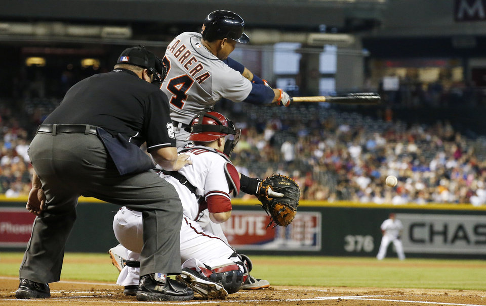 Photo - Detroit Tigers' Miguel Cabrera, top, connects on a run-scoring single as Arizona Diamondbacks' Miguel Montero, bottom right, and umpire Fieldin Culbreth, left, look on during the first inning of a baseball game on Tuesday, July 22, 2014, in Phoenix. (AP Photo)