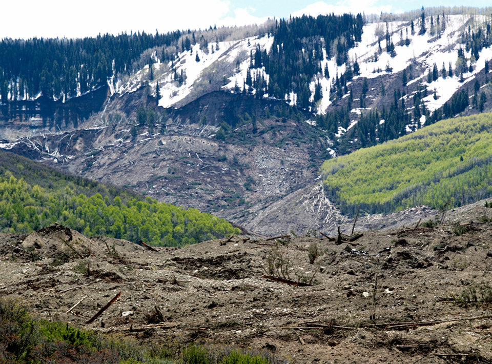 Photo - The results of a three-mile long mudslide are piled below Grand Mesa, where the slide started, background, in a remote part of western Colorado near the small town of Collbran Monday, May 26, 2014. Rescue teams are searching for three men missing after a half-mile stretch of a ridge saturated with rain collapsed. (AP Photo/Grand Junction Daily Sentinel, Dean Humphrey)