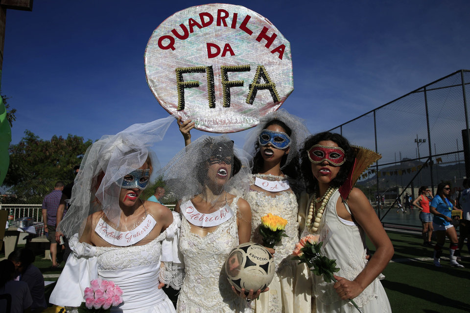 Photo - Women wearing wedding dresses and vampire make up pose for a picture while holding a sign that reads in Portuguese,