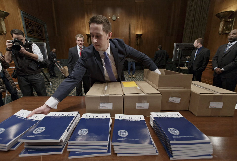 Photo - Copies of President Barack Obama's proposed budget for fiscal 2015 are set out for distribution by Senate Budget Committee Clerk Adam Kamp, on Capitol Hill in Washington, Tuesday, March 4, 2014. Obama's fiscal blueprint, which he is sending Congress today, was expected to include proposals to upgrade aging highways and railroads, finance more pre-kindergarten programs and enhance job training.  (AP Photo/J. Scott Applewhite)
