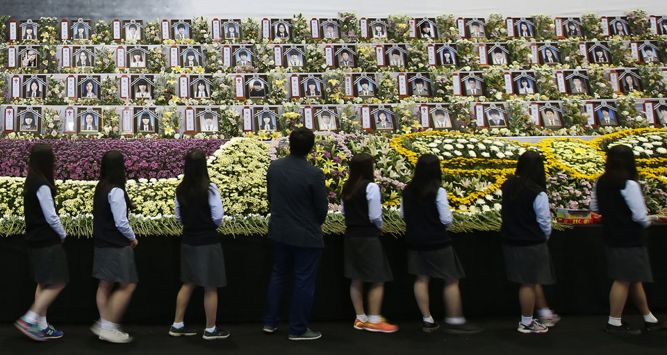 Photo - Middle school students watch portraits of the victims of the sunken ferry Sewol at a group memorial altar in Ansan, South Korea, Thursday, May 15, 2014.  Prosecutors indicted the captain of the sunken South Korean ferry and three crew members on homicide charges Thursday, alleging they were negligent and failed to protect more than 300 people missing or dead in the disaster. Less serious indictments were issued against the 11 other crew members responsible for navigating the vessel.  (AP Photo/Yonhap)  KOREA OUT