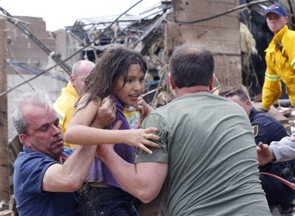 Photo - A child is pulled from the rubble of the Plaza Towers Elementary School in Moore, Okla., and passed along to rescuers Monday, May 20, 2013. A tornado as much as a mile (1.6 kilometers) wide with winds up to 200 mph (320 kph) roared through the Oklahoma City suburbs Monday, flattening entire neighborhoods, setting buildings on fire and landing a direct blow on an elementary school.(AP Photo Sue Ogrocki)