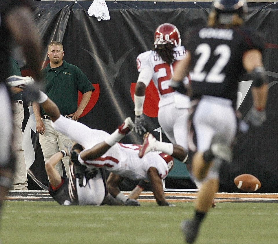 Photo - Jonathan Nelson (3) strips the ball from Cincinnati receiver DJ Woods near the goal line after a long carry during the first half of the college football game between the University of Oklahoma Sooners (OU) and the University of Cincinnati Bearcats (UC) at Paul Brown Stadium on Saturday, Sept. 25, 2010, in Cincinnati, Ohio. Quinton Carter (20) recovered the ball for a touchback.  Photo by Steve Sisney, The Oklahoman