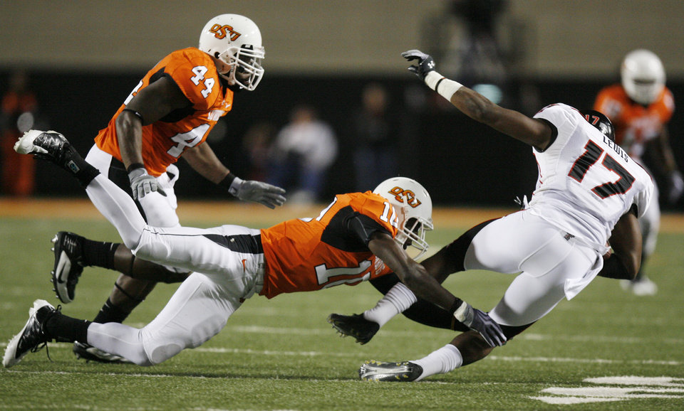 Photo - Cowboy Markelle Martin (10) brings down Detron Lewis (17) as Donald Booker (44) closes in during the college football game between Oklahoma State University (OSU) and Texas Tech University (TT) at Boone Pickens Stadium in Stillwater, Okla. Saturday, Nov. 14, 2009. Photo by Sarah Phipps, The Oklahoman ORG XMIT: KOD