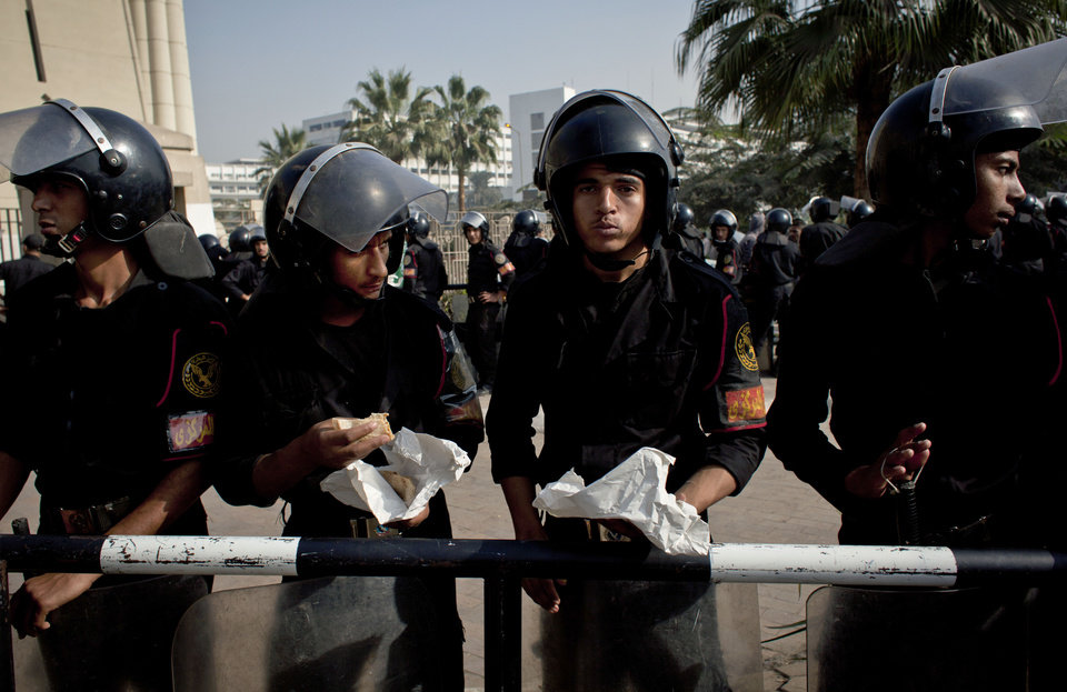 Photo - Riot policemen eat their lunch as they stand guard in front of Egypt's top court during a protest for supporters of Egyptian President Mohammed Morsi, unseen, in Cairo, Egypt, Monday, Dec. 3, 2012. The Egyptian president's top legal adviser says the country's election commission has begun preparations for the referendum on Dec. 15 on a highly contentious draft constitution. (AP Photo/Nasser Nasser)