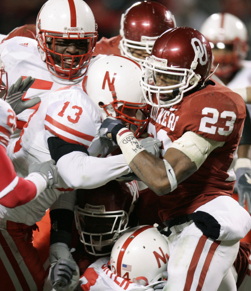 Photo - Allen Patrick of  OU is tackled by Ola Dagunduro, left, and Corey McKean of  Nebraska in the second half of the Big 12 Championship game during the University of Oklahoma Sooners ( OU) college  football game against the University of  Nebraska Cornhuskers (NU) at Arrowhead Stadium, on Saturday, Dec. 2, 2006, in Kansas City, Mo. By Bryan Terry, The Oklahoman