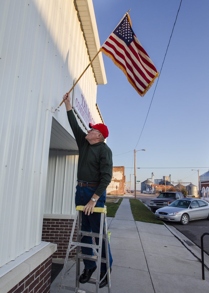 Rich Hauberg places a flag on the community hall in the small village of Talmage, Neb., Tuesday, Nov. 6, 2012, before the polling place opens on Election Day. Hauberg was wed in this same hall 50 years ago. (AP Photo/Nati Harnik)