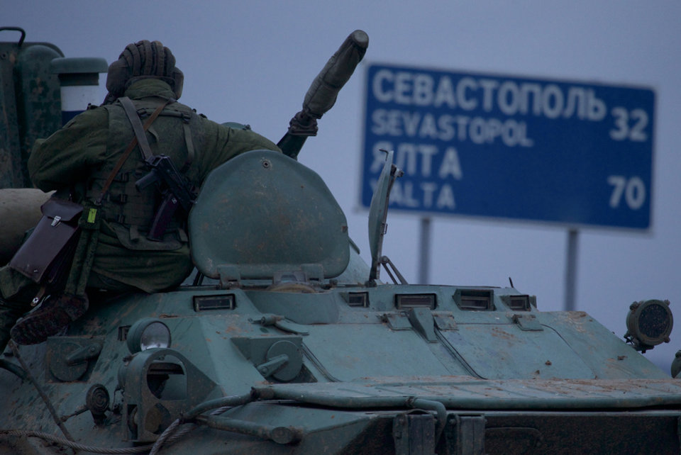 Photo - A soldier rests atop a Russian armored personnel carriers with a road sign reading