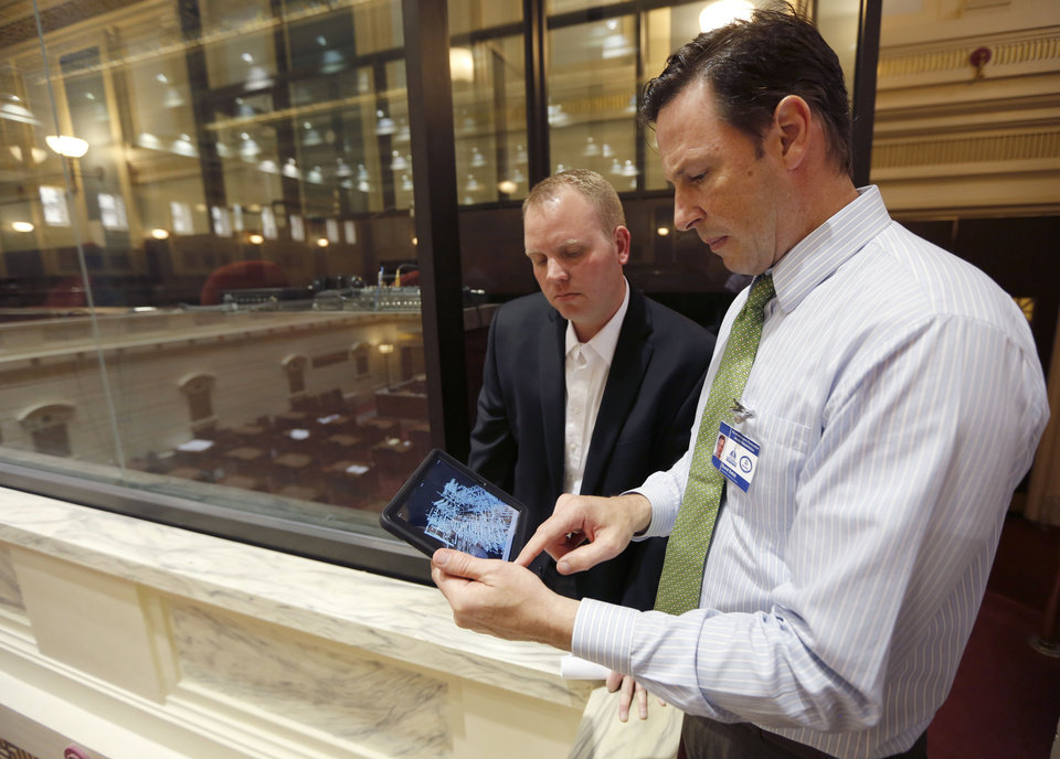 Photo - Director of Mechanical Engineering Brian Sauer, left, and David Ketch, Senior Architect for FSB and part of a team of architects and engineers producing a 3D map of the State Capitol building, use an I-pad to demonstrate the mechanical systems in the Senate Chambers of the Oklahoma State Capitol in Oklahoma City, OK, Friday, May 29, 2015. The results of the mapping will be used to guide the Capitol's biggest-ever remodel and repair project.   Photo by Paul Hellstern, The Oklahoman