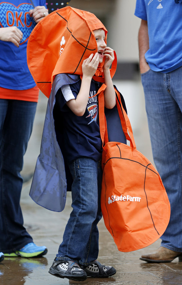 Carter McCollough, 7, of Bixby tries to stay dry outside the arena before Game 5 in the second round of the NBA playoffs between the Oklahoma City Thunder and the Memphis Grizzlies at Chesapeake Energy Arena in Oklahoma City, Wednesday, May 15, 2013.  Photo by Bryan Terry, The Oklahoman