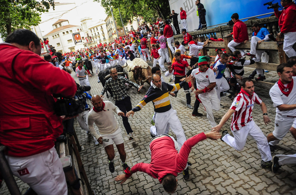 Photo - A runner falls, bottom, as revelers run ahead Garcigrande fighting bulls before they come into in the bull ring, during the running of the bulls,  at the San Fermin festival, in Pamplona, Spain, Thursday, July 10, 2014. Revelers from around the world arrive to Pamplona every year to take part in some of the eight days of the running of the bulls glorified by Ernest Hemingway's 1926 novel