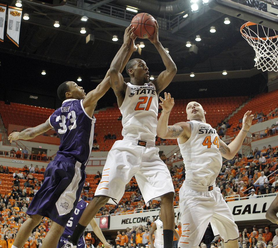 Oklahoma State's Kamari Murphy (21) pulls in a rebound in front of Philip Jurick (44) and TCU's Garlon Green (33) during the college basketball game between Oklahoma State University Cowboys (OSU) and Texas Christian University Horned Frogs (TCU) at Gallagher-Iba Arena on Wednesday Jan. 9, 2013, in Stillwater, Okla. 