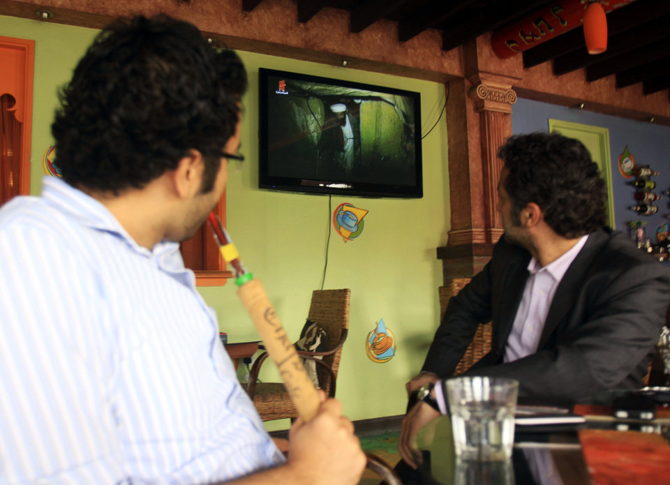 Photo - Bahraini men smoke and watch a TV news report on the killing of Al-Qaida leader Osama bin Laden,  at a coffee shop in Sitra, Bahrain, on Monday, May 2, 2011.   al-Qaida chief  Osama bin Laden was slain at a fortress-like compound in Abbottabad, Pakistan, early Monday in a firefight with U.S. forces, ending a manhunt that spanned a decade.  (AP Photo/Hasan Jamali) ORG XMIT: XHJ103