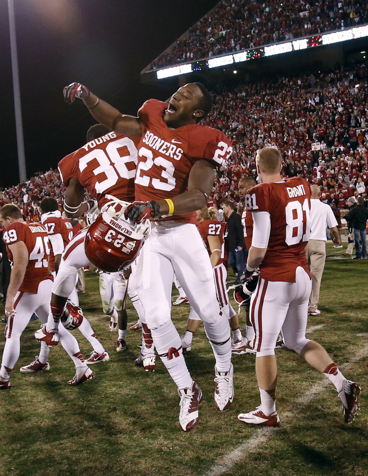 Photo - Oklahoma's Danzel Williams (23) and Brandon Young (38) leap at the conclusion of the Bedlam college football game in which  the University of Oklahoma Sooners (OU) defeated the Oklahoma State University Cowboys (OSU) 51-48 in overtime at Gaylord Family-Oklahoma Memorial Stadium in Norman, Okla., Saturday, Nov. 24, 2012. Photo by Steve Sisney, The Oklahoman