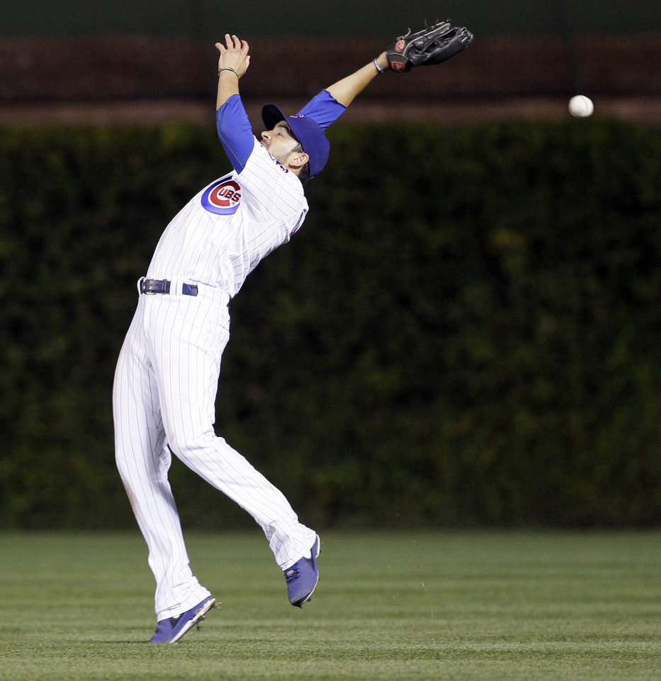 Photo -   Chicago Cubs right fielder David DeJesus misses a fly ball by Cincinnati Reds' Brandon Phillips during the 11th inning of a baseball game in Chicago, Wednesday, Sept. 19, 2012. DeJesus was charged with an error. (AP Photo/Nam Y. Huh)