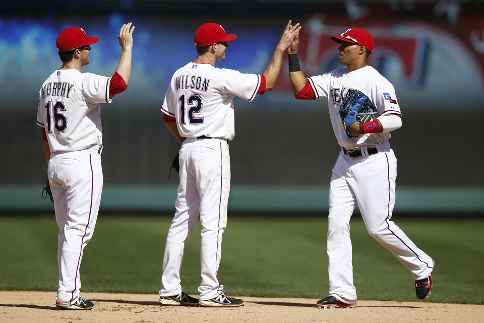 Photo - Texas Rangers' Donnie Murphy and Josh Wilson line up to celebrate with Leonys Martin following a baseball game against the Houston Astros, Sunday, April 13, 2014, in Arlington, Texas. The Rangers won 1-0. (AP Photo/Jim Cowsert)